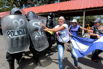 A demonstrator clashes with riot police during a protest against Nicaraguan President Daniel Ortega's government in Managua