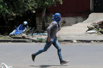 A demonstrator runs during a clash with supporters of Nicaraguan president Daniel Ortega's government in Managua