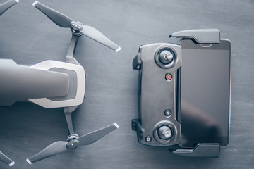 Wall Mural - Mate color. A new black drone on a black table. The concept of using drones in life and industry. Close up Top view Remote control and smartphone macro Details. Copy space.