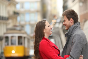 Cheerful couple looking each other in the street