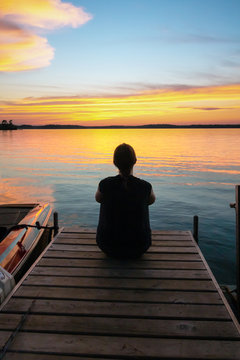 Beautiful sunrise sunset scene of a young woman sitting at the end of a pier looking at the colorful sky. Concepts of vacation, travel, tranquility