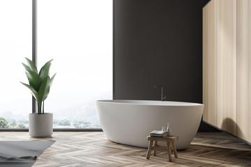 White bathtub near loft window in gray bathroom