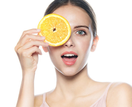 beauty portrait of attractive young caucasian happy woman isolated on white studio shot eating orange fruit fresh healthy food raw diet