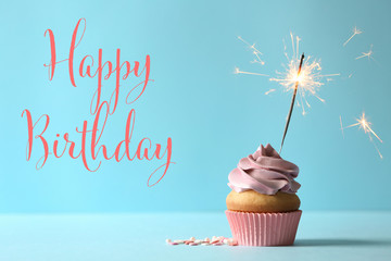 Delicious birthday cupcake with burning sparkler and space for text on color background