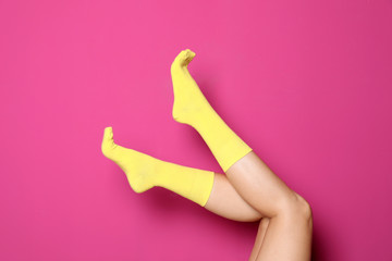 Woman wearing bright socks on color background