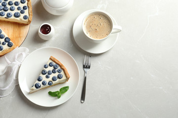 Flat lay composition with piece of tasty blueberry cake and space for text on gray table