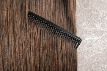 Beautiful hair and comb on grey background, top view