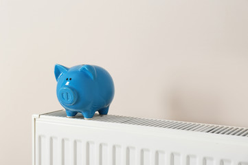 Piggy bank on heating radiator against light background