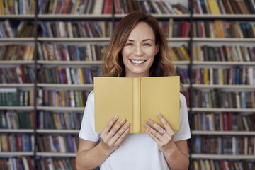 Portrait of smiling woman model with opened book in a library, bookshelf behind, long hair. Hipster college student lady..