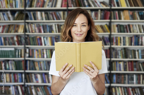 Portrait Of Smiling Woman Model Reading Text With Opened Book In A Library Bookshelf Behind