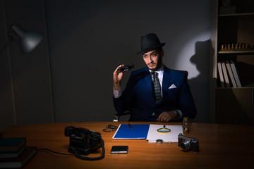 Detective sitting in dark room in vintage concept