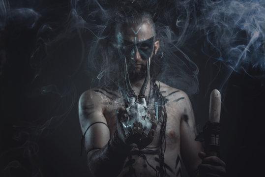 Dark tribal shaman or warlock summoning spirits using a deer skull and his ritual staff, halloween concept