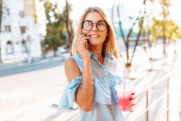 Portrait of a beautiful girl student, wearing glasses, talking on the phone in a good mood, and holding a cocktail