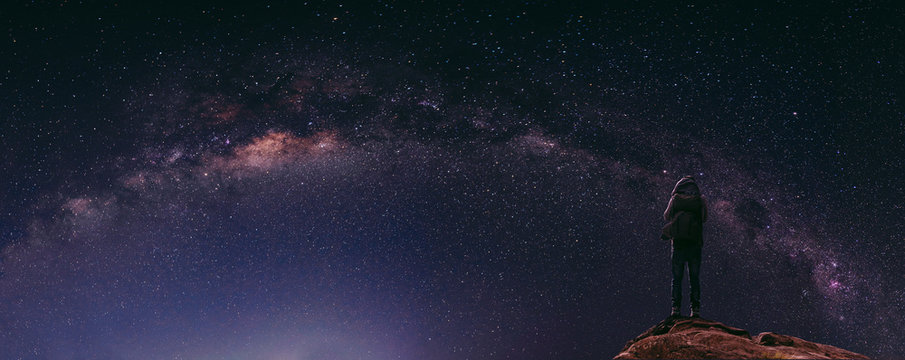 Night sky full of star and milky way, with traveller with backpack enjoying beautiful sky at night