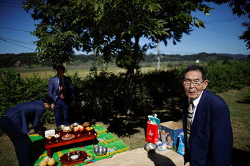 Ko Ju-rak, who was born in what is now North Korea, prepares for a memorial service for his North Korean family members, in front of a barbed-wire fence near the demilitarized zone separating the two Koreas, in Paju