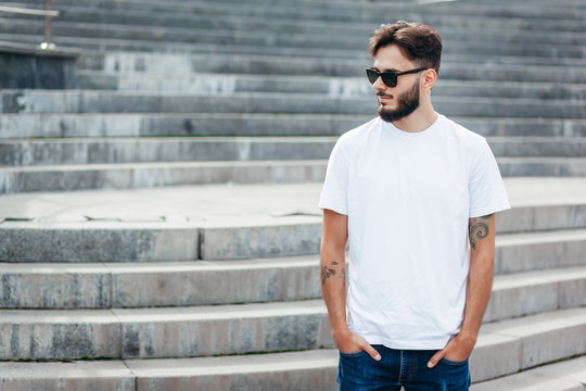 A young stylish man with a beard in a white T-shirt and glasses. Street photo
