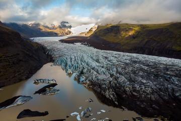 Glacier and brown lake