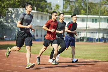 young asian athletes running on track