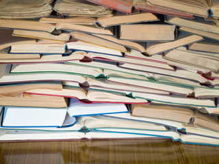 a lot of opened old and used hardback books or text books. Books and reading are essential for self improvement, gaining knowledge and success in our careers, business and personal lives.