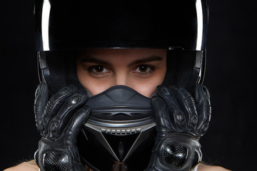 Beautiful young woman in black leather gloves and protective motorbike helmet in studio. Attractive self determined female motocycle racer wearing hands and body protection from falls and accidents Wall mural