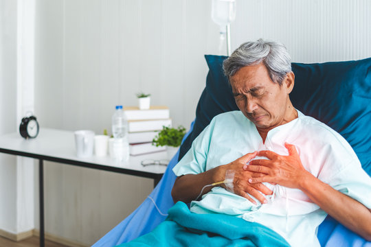 Old patient man holding heart for heart attack concept