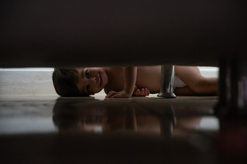 Cute baby boy toddler - Under the bed lying..