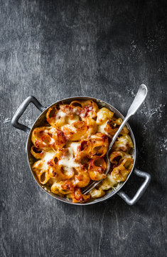 Tomato sauce mac and cheese, baked in vintage pan on a wooden dark background, top view