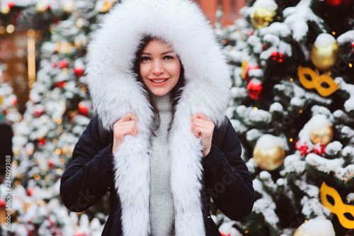 84685b006e45 christmas portrait of happy young woman walking in winter snowy city ...