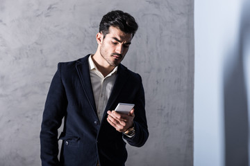 A serious handsome young businessman in a black suit using a smartphone in front of a grey wall in a studio.