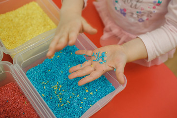 Child hands playing with colored rice in the sensory box. Baby's sensory educational kit