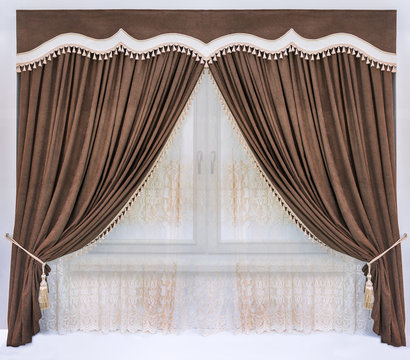 Decoration of the interior of the living room or bedroom in the classical style. A brown curtain of the soft velvet fabric, a figured pelmet with an insert from a contrast material, and tulle