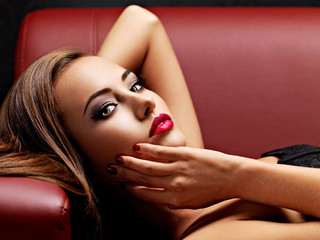 Beautiful  woman with bright eye makeup and  red lips lying on the sofa