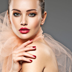 fashion woman with stylish makeup, red nails and lips wearing beige scarf