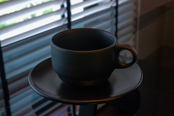 An empty black coffee cup is on the glass table next to the window.