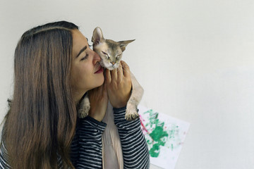young attractive brunette woman playing with a Sphinx kitten hugging an animal