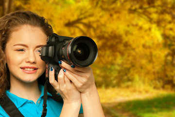 Young pretty girl with camera in autumn park