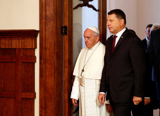 Pope Francis and Latvian president Raimonds Vejonis arrive at a welcoming ceremony for Pope Francis in Riga
