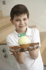 Little boy holding cupcake