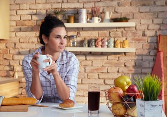 Young woman drinks breakfast coffee in pyjama