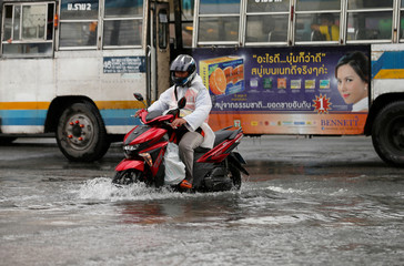A man drives his motorbike on a flooded street in Bangkok