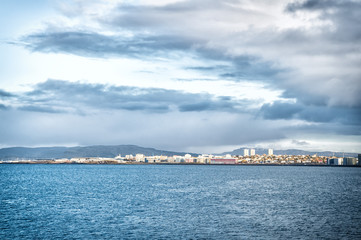 City on sea coast Iceland. Scandinavian seascape concept. Calm water surface and city with high buildings modern architecture. Scandinavian city at seashore. Reykjavik seascape dramatic cloudy sky