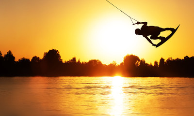 Wake Board a man does a trick at sunset on the Board on the water splashes Wall mural