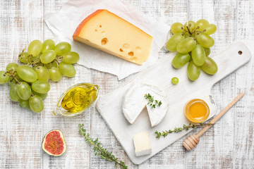 Camembert, yellow cheese, fruits and herbs on white wooden background. Cheese plate, appetizer plate. Top view