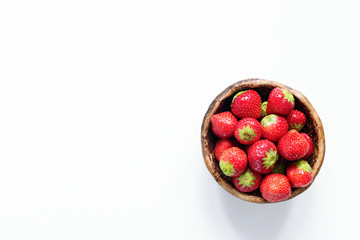 Strawberries in bowl on white background. Top view, copy space for text. Fresh red berries