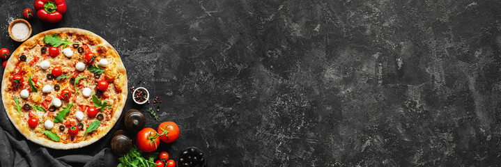 Italian pizza and pizza cooking ingredients on black concrete background. Tomatoes on vine, mozzarella, black olives, herbs and spices. Copy space for text. Banner composition
