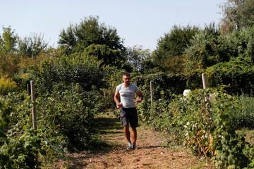 Komaromi, former editor at the daily Nepszabadsag walks in his garden in Szigetszentmiklos