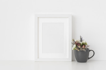 White A5 portrait frame mockup with dried field wild flowers in mug on white wall background. Empty frame, poster mock up for presentation design. Template frame for text, lettering, modern art.