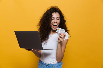 Photo of young woman 20s wearing casual clothes holding black laptop and credit card, isolated over yellow background