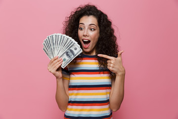 Image of successful woman 20s with curly hair holding fan of dollar money, isolated over pink background