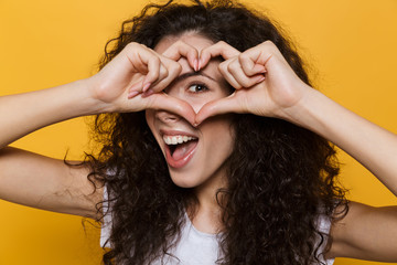Photo of caucasian woman 20s with curly hair smiling and showing heart shape with fingers, isolated over yellow background